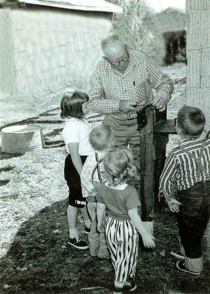 Grampie sharpening a saw as his grandchildren looked on.  I'm second from the left.