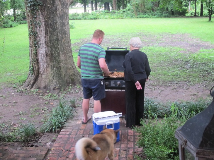 Preparing the rehearsal dinner. The homeowner is picking up a new recipe from the grill master.